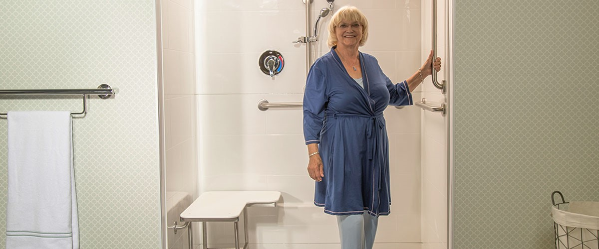 women in blue robe using grab bar in accessible shower